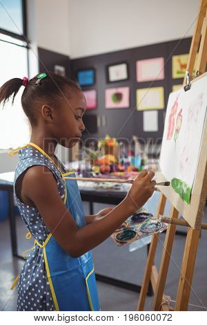 Side view of girl painting on canvas in classroom
