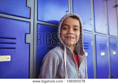Portrait of smiling boy standing by lockers at school