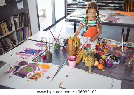 High angle view of concentrated girl painting on white paper at desk in classroom
