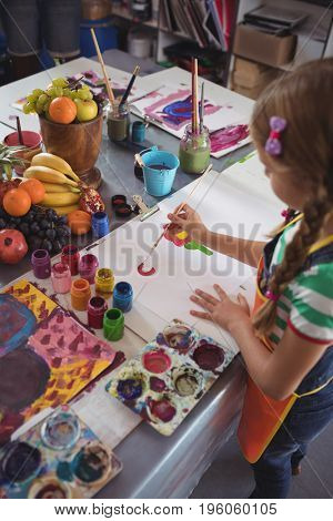 High angle view of girl painting on white paper at desk in classroom