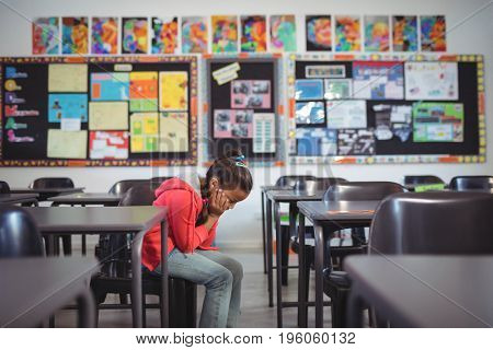 Side view of girl sitting on chair in classroom at school
