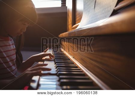 Focused girl practicing piano in classroom at music school
