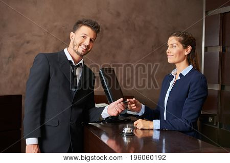 Smiling guest paying with his credit card at hotel reception