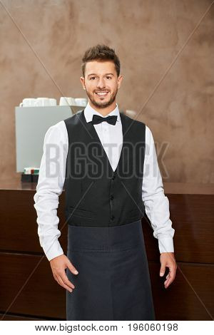 Friendly waiter in uniform in a hotel restaurant
