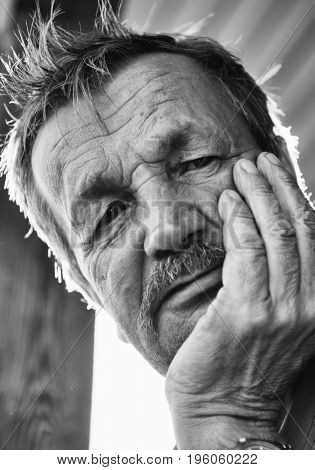 Thoughtful mustachioed elderly man. Close-up of a black and white portrait.