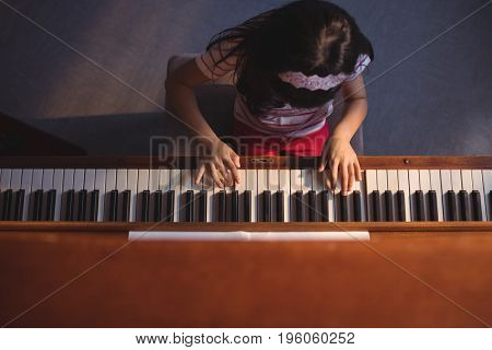 Overhead view of elementary girl playing piano in classroom at music school