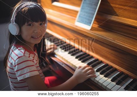 High angle portrait of girl wearing headphones while practicing piano in classroom at music school