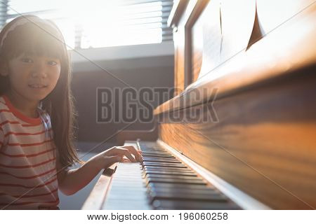 Portrait of girl practicing piano in class at music school