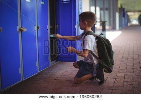 Side view of boy keeping books in locker at school corridor