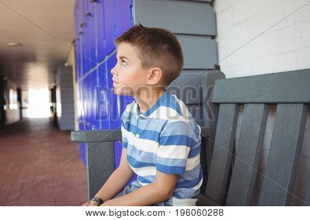 Thoughtful boy sitting on bench by lockers in corridor at school
