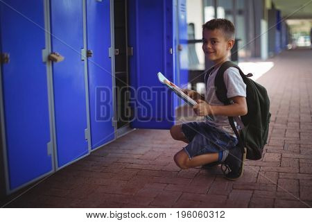 Portrait of boy holding books by open locker at school corridor