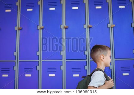 Boy carrying backpack against lockers at school