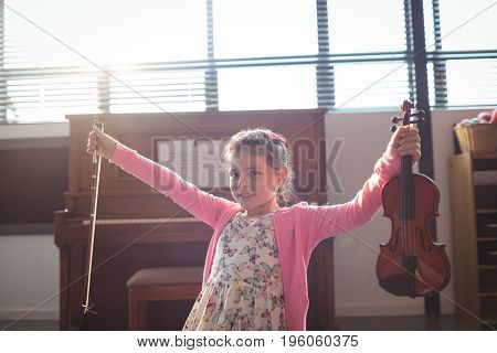 Portrait smiling girl holding violin with arms outstretched at music classroom