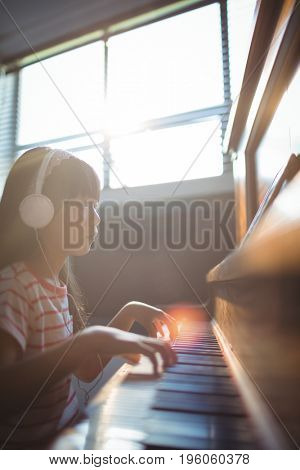 Concentrated girl looking at digital tablet while practicing piano in classroom at music school