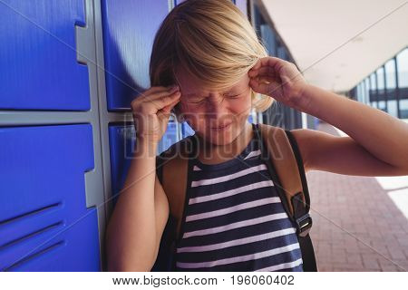 Schoolboy suffering from headache while standing by lockers in corridor at school