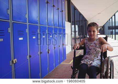 Portrait of schoolgirl sitting on wheelchair by lockers in corridor at school