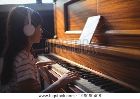 Side view of girl looking at digital tablet while practicing piano in classroom at music school