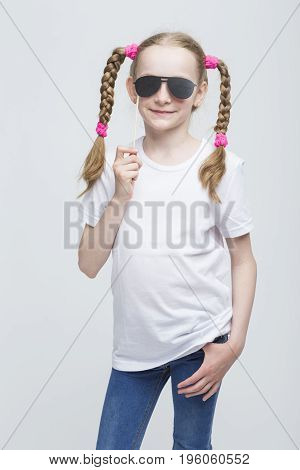 Kids Ideas and Concepts. Portrait of Positive Caucasian Blond Girl With Pigtails Posing with Artistic Spectacles Against White Background. Vertical Image Composition