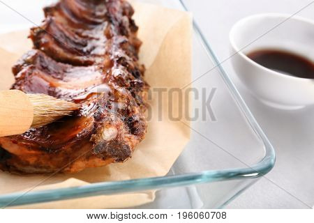 Baking tray with delicious pork ribs on table, closeup