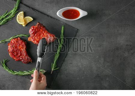 Female hand taking pork ribs with kitchen tongs over slate plate