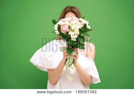 Young woman holding beautiful bouquet with white freesia on color background