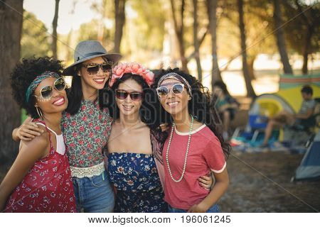 Portrait of smiling female friends standing together at campsite