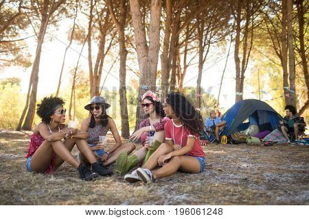 Smiling female friends sitting together on field at campsite