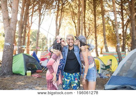 Females kissing male friends standing on field at campsite