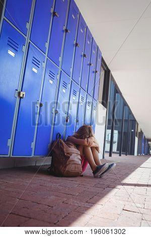 Full length of schoolgirl sitting by lockers in corridor at school