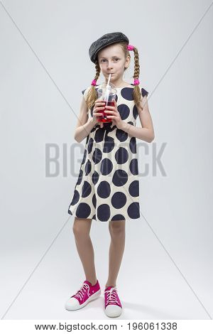 Full Length Portrait of Funny Caucasian Girl With Pigtails Posing in Gray Velvel Cap and Polka Dot Dress with Cup of Red Juice. Drinking Through Straw. Against White. Vertical Image