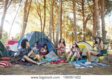 Young friends sitting together by tents on field at campsite