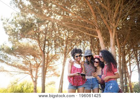 Smiling female friends using mobile phone against trees at campsite