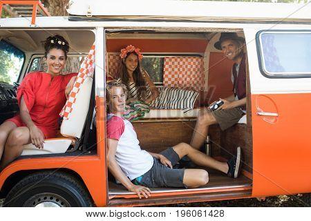 Portrait of smiling young friends resting together in camper van