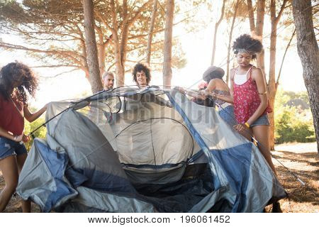 Young female friends setting up tent at countryside