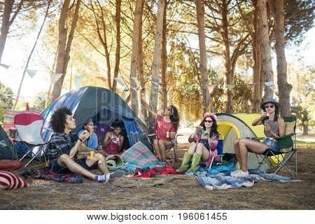 Young friends enjoying together by tents on field at campsite