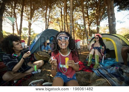 Happy young woman holding bubble wand with friends in background at campsite