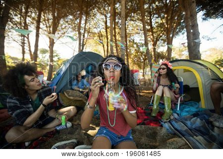 Young woman blowing bubble wand with friends in background at campsite