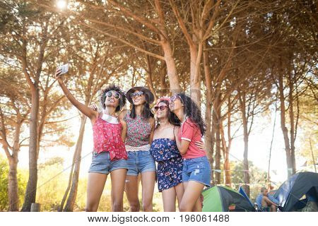 Happy female friends taking selfie while standing at campsite