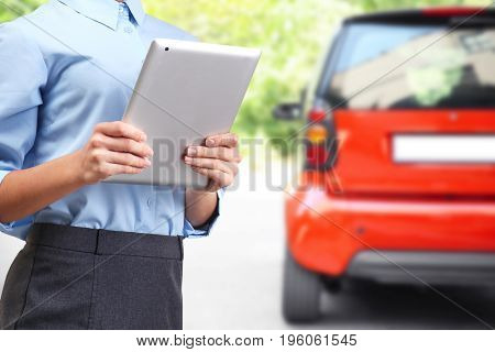 Insurance agent holding tablet and car on background