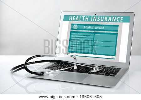 Laptop and stethoscope on light background. Health insurance concept