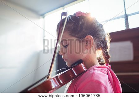 Side view of girl student rehearsing violin in music class