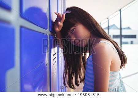 Portrait of sad girl leaning on lockers in corridor at school