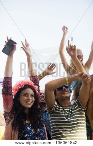 Happy fans with arms raised enjoying against sky at music festival