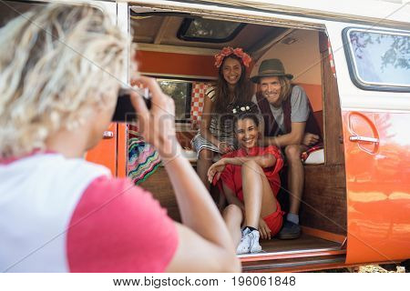Man photographing smiling friends through camera sitting in camper van