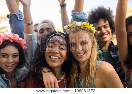 Portrait of smiling friends enjoying together at music festival