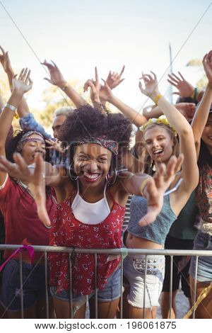 Portrait of cheerful young woman by railing enjoying at music festival