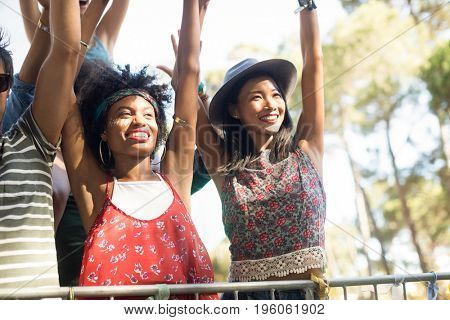 Happy females enjoying with arms raised at music festival