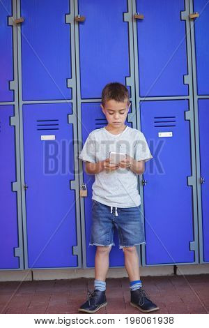 Full length of boy using mobile phone while standing against lockers at school