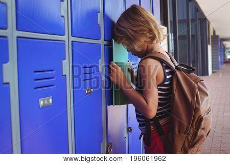 Sad boy leaning on lockers in corridor at school