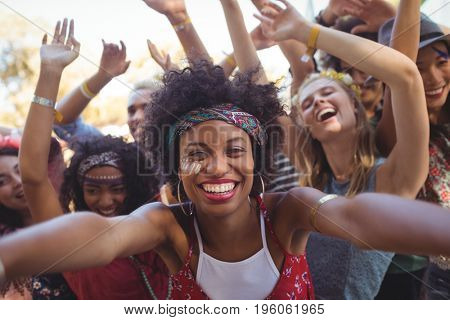 Portrait of cheerful young woman enjoying at music festival